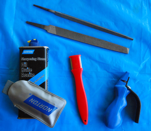 At the top of the group, a three-square or triangular fine file and a flat bastard file. Centered below them is red handle with two tiny, fine files at its business end. The blue pistol grip sharpener holds a honing stone notched to accept a double-edged pruning blade. The honing stone (in the Norton package) is small enough that I can use it to stroke a blade rather than the other way 'round.
