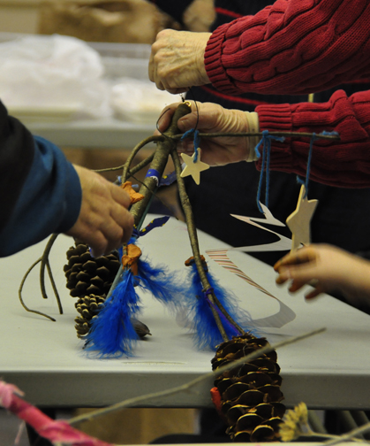 """Natural Mobiles"" in Growing Concerns #647: Have fun with kids during late winter cabin fever days. Collect from the garden, add bright color with scraps of biodegradable cotton cloth, yarn, modeling clay, and use a pine branch to hang it in the garden."