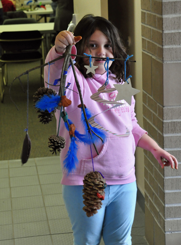 Megan's mobile features stars, cones and a Kentucky coffee tree pod tied on with blue yard, and matching blue feathers anchored with bits of red clay