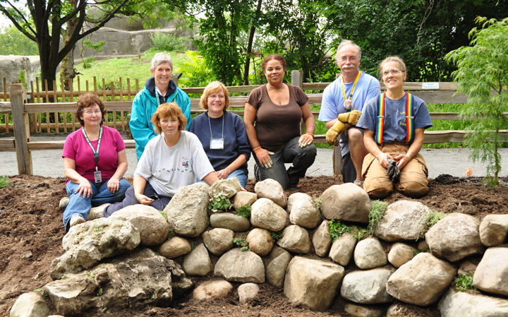 They aren't only names on a list, they're faces we know and hands who have helped, as here at one of our Detroit Zoo Adopt-A-Gardens.  From left: Julia Moncecchi, Michele Armstrong, Susan Campbell, Anne Crimmins, Gail Anderson, Keith Heraty and Janet take a breath atop they wall they just built. (Some others vamoosed when the camera appeared: Paul and Priscilla Needle, for instance, are currently invisible, rock solid support!)
